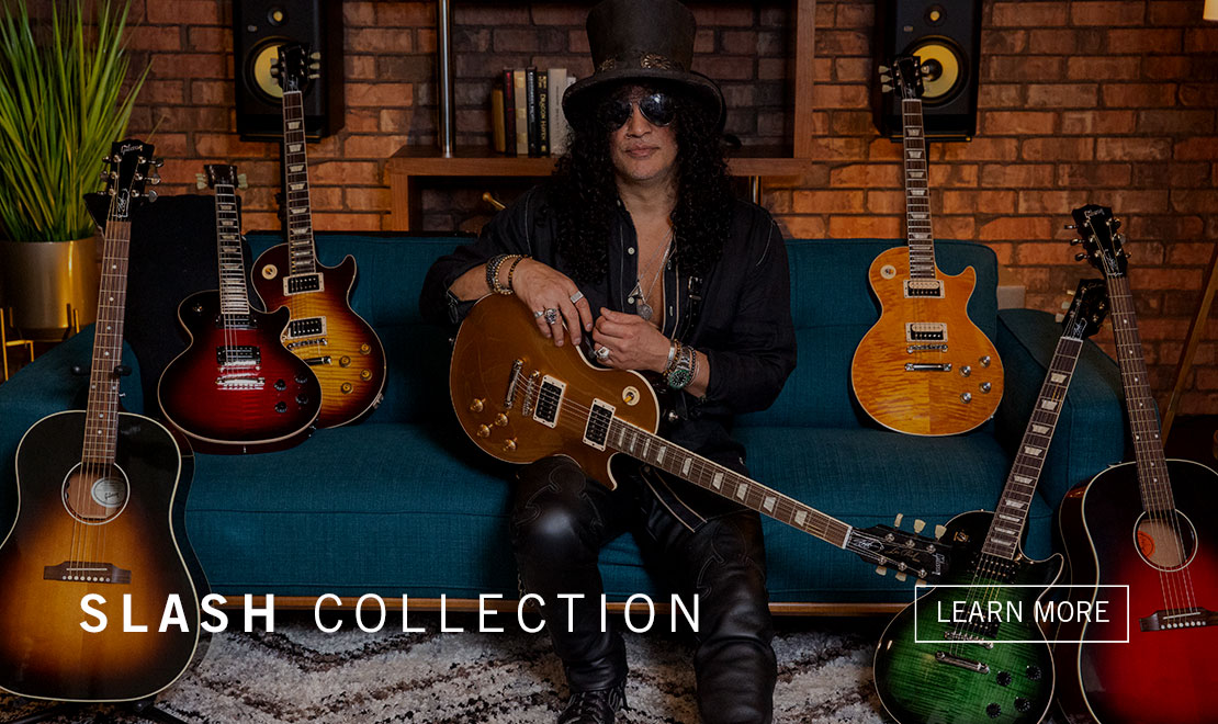 "Slash poses on a couch with his Signatture series of guitars, part of the Gibson Slash Collection. Featured in this photo is ""Victoria,"" The Les Paul Standard Goldtop just added to the Gibson Slash Collection."